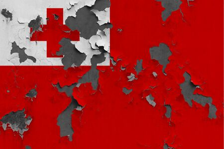 Tonga flag close up painted, damaged and dirty on wall peeling off paint to see concrete surface. Vintage National Concept.