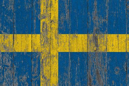 Sweden flag on grunge scratched wooden surface. National vintage background. Old wooden table scratched flag surface. Archivio Fotografico