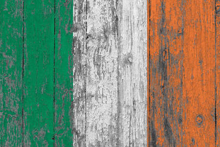 Ireland flag on grunge scratched wooden surface. National vintage background. Old wooden table scratched flag surface.