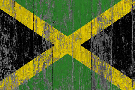 Jamaica flag on grunge scratched wooden surface. National vintage background. Old wooden table scratched flag surface.