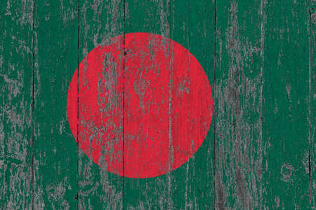 Bangladesh flag on grunge scratched wooden surface. National vintage background. Old wooden table scratched flag surface.