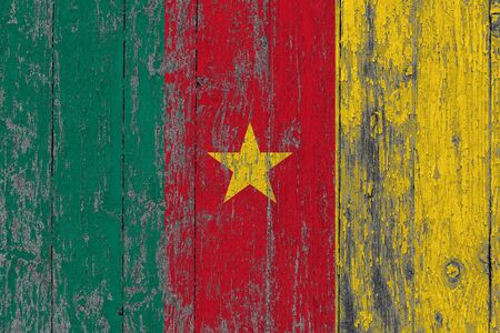 Cameroon flag on grunge scratched wooden surface. National vintage background. Old wooden table scratched flag surface.