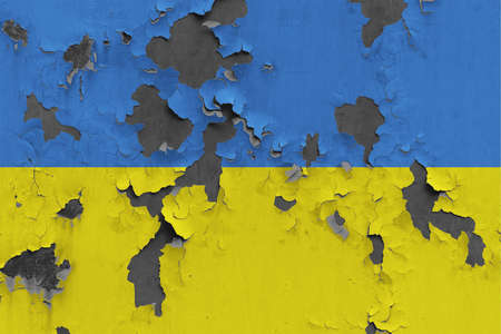 Ukraine flag close up painted, damaged and dirty on wall peeling off paint to see concrete surface. Vintage National Concept.