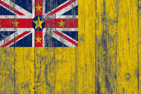 Niue flag on grunge scratched wooden surface. National vintage background. Old wooden table scratched flag surface.