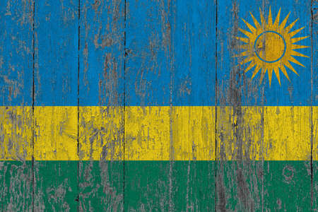 Rwanda flag on grunge scratched wooden surface. National vintage background. Old wooden table scratched flag surface.
