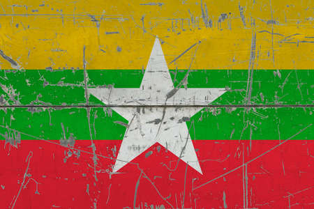 Myanmar flag painted on cracked dirty surface. National pattern on vintage style surface. Scratched and weathered concept.