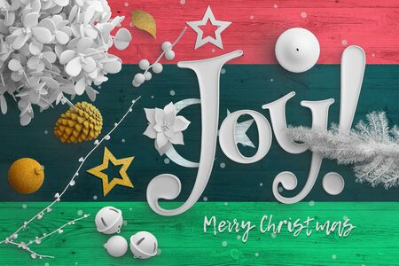 Libya flag on wooden table with joy text. Christmas and new year background, celebration national concept with white decor. Foto de archivo