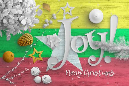 Myanmar flag on wooden table with joy text. Christmas and new year background, celebration national concept with white decor.