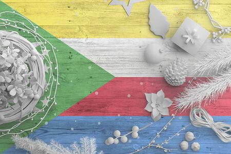 Comoros flag on wooden table with snow objects. Christmas and new year background, celebration national concept with white decor.