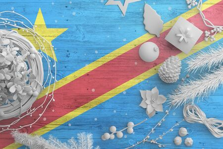 Congo flag on wooden table with snow objects. Christmas and new year background, celebration national concept with white decor.