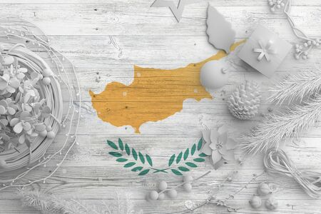 Cyprus flag on wooden table with snow objects. Christmas and new year background, celebration national concept with white decor.