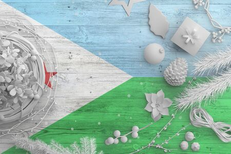 Djibouti flag on wooden table with snow objects. Christmas and new year background, celebration national concept with white decor.