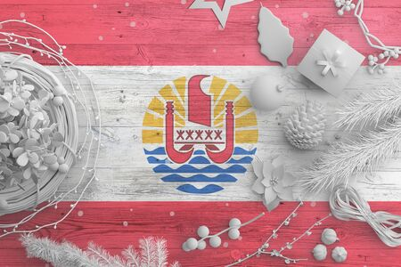 French Polynesia flag on wooden table with snow objects. Christmas and new year background, celebration national concept with white decor.