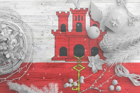 Gibraltar flag on wooden table with snow objects. Christmas and new year background, celebration national concept with white decor. Foto de archivo