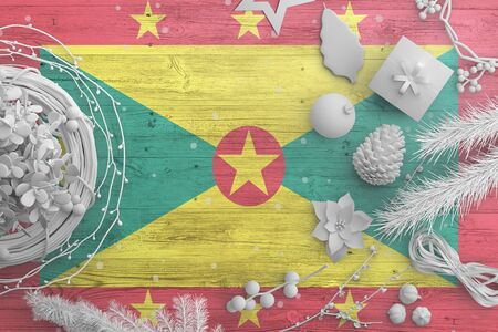 Grenada flag on wooden table with snow objects. Christmas and new year background, celebration national concept with white decor.
