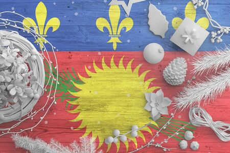 Guadeloupe flag on wooden table with snow objects. Christmas and new year background, celebration national concept with white decor.