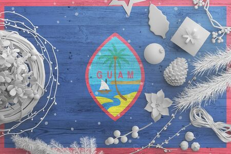 Guam flag on wooden table with snow objects. Christmas and new year background, celebration national concept with white decor. Foto de archivo