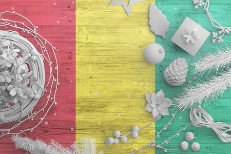 Guinea Bissau flag on wooden table with snow objects. Christmas and new year background, celebration national concept with white decor.