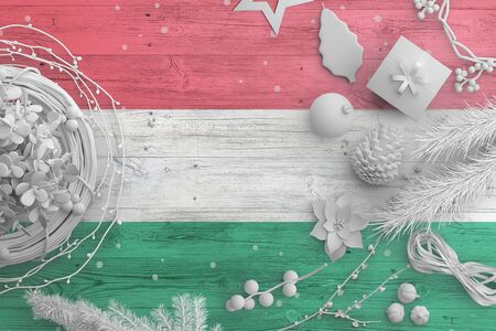 Hungary flag on wooden table with snow objects. Christmas and new year background, celebration national concept with white decor.