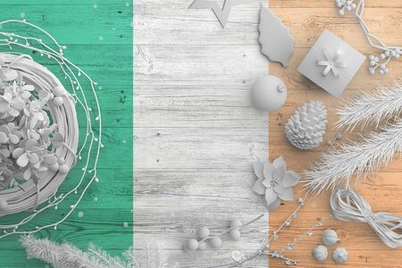 Ireland flag on wooden table with snow objects. Christmas and new year background, celebration national concept with white decor.