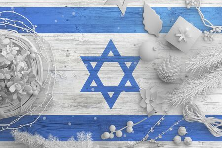 Israel flag on wooden table with snow objects. Christmas and new year background, celebration national concept with white decor.