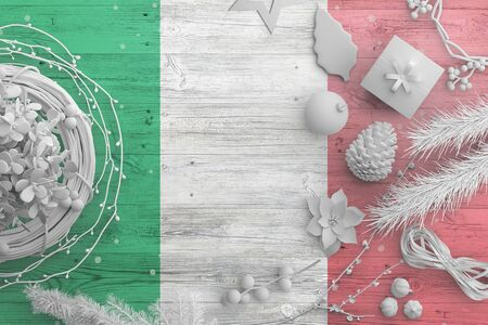 Italy flag on wooden table with snow objects. Christmas and new year background, celebration national concept with white decor.