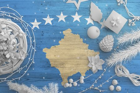 Kosovo flag on wooden table with snow objects. Christmas and new year background, celebration national concept with white decor.