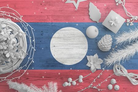 Laos flag on wooden table with snow objects. Christmas and new year background, celebration national concept with white decor.
