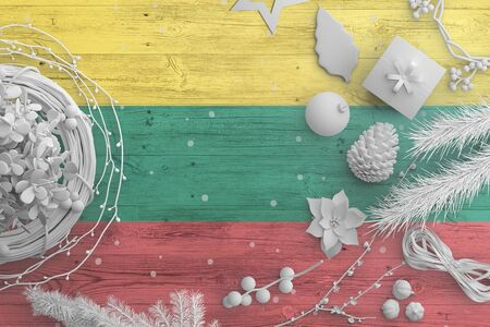 Lithuania flag on wooden table with snow objects. Christmas and new year background, celebration national concept with white decor. 版權商用圖片