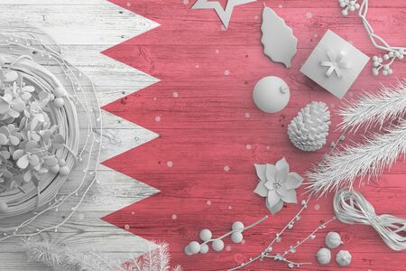 Bahrain flag on wooden table with snow objects. Christmas and new year background, celebration national concept with white decor. Foto de archivo