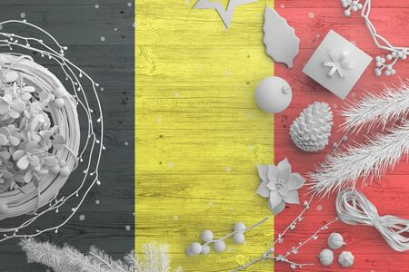 Belgium flag on wooden table with snow objects. Christmas and new year background, celebration national concept with white decor.