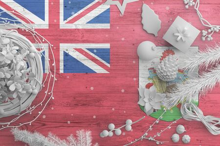 Bermuda flag on wooden table with snow objects. Christmas and new year background, celebration national concept with white decor.