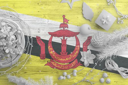 Brunei flag on wooden table with snow objects. Christmas and new year background, celebration national concept with white decor. Foto de archivo