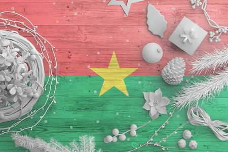 Burkina Faso flag on wooden table with snow objects. Christmas and new year background, celebration national concept with white decor.