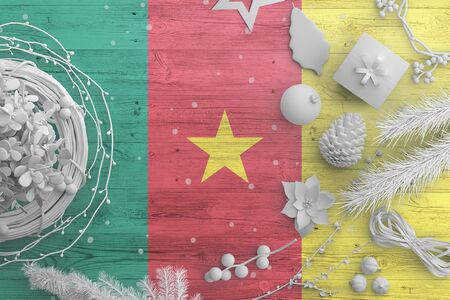 Cameroon flag on wooden table with snow objects. Christmas and new year background, celebration national concept with white decor.