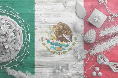 Mexico flag on wooden table with snow objects. Christmas and new year background, celebration national concept with white decor.
