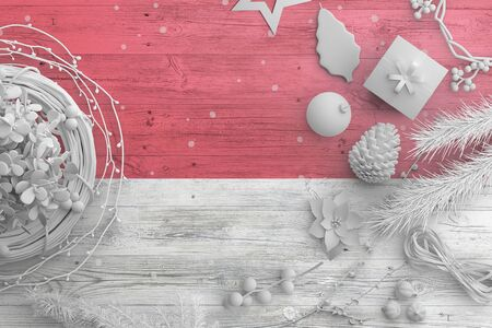 Monaco flag on wooden table with snow objects. Christmas and new year background, celebration national concept with white decor.