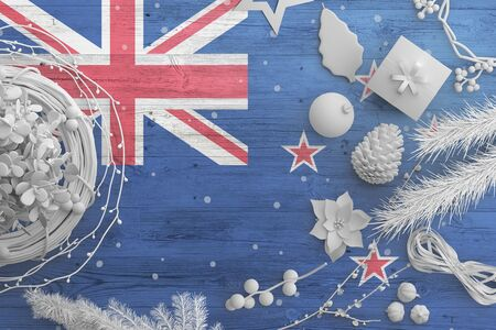 New Zealand flag on wooden table with snow objects. Christmas and new year background, celebration national concept with white decor.