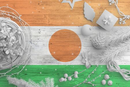 Niger flag on wooden table with snow objects. Christmas and new year background, celebration national concept with white decor.