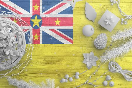 Niue flag on wooden table with snow objects. Christmas and new year background, celebration national concept with white decor. Foto de archivo