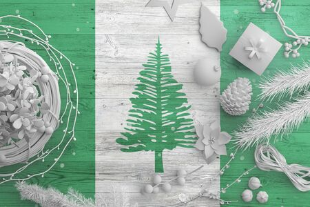 Norfolk Island flag on wooden table with snow objects. Christmas and new year background, celebration national concept with white decor.