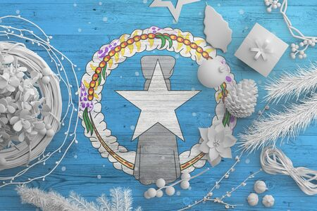 Northern Mariana Islands flag on wooden table with snow objects. Christmas and new year background, celebration national concept with white decor.