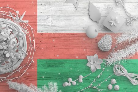 Oman flag on wooden table with snow objects. Christmas and new year background, celebration national concept with white decor. Foto de archivo