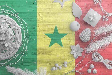 Senegal flag on wooden table with snow objects. Christmas and new year background, celebration national concept with white decor.