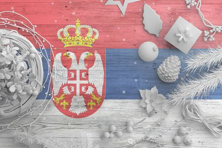 Serbia flag on wooden table with snow objects. Christmas and new year background, celebration national concept with white decor.