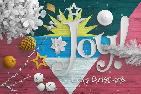 Antigua and Barbuda flag on wooden table with joy text. Christmas and new year background, celebration national concept with white decor.