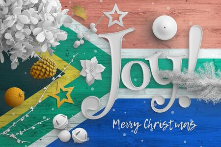 South Africa flag on wooden table with joy text. Christmas and new year background, celebration national concept with white decor.