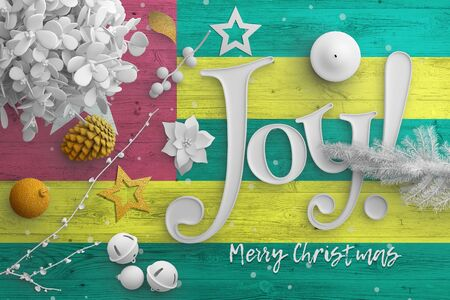Togo flag on wooden table with joy text. Christmas and new year background, celebration national concept with white decor. Foto de archivo