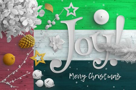 United Arab Emirates flag on wooden table with joy text. Christmas and new year background, celebration national concept with white decor.