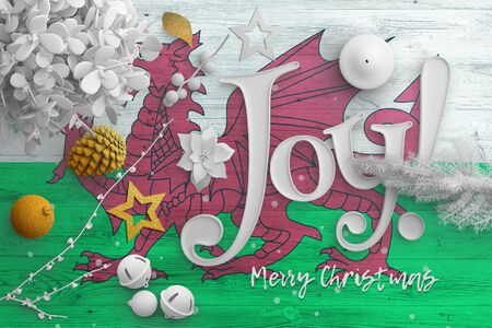 Wales flag on wooden table with joy text. Christmas and new year background, celebration national concept with white decor. Foto de archivo